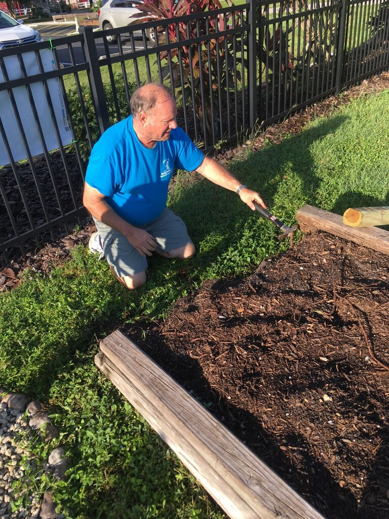 Volunteer Dave Bowman helps to repair one of the Community Garden beds.